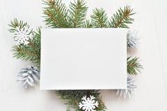 Tomt vitt ark av papper på en bakgrund för vit jul av granfilialer och kottar Bokstav på xmas, modell Lekmanna- lägenhet fotografering för bildbyråer