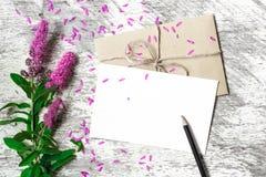 Tomt vitt hälsningkort, kuvert och blyertspenna med purpurfärgade vildblommor fotografering för bildbyråer
