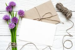 Tomt vitt hälsningkort med den purpurfärgade vildblommabuketten och kuvert med ett rep över den vita trätabellen Royaltyfri Foto
