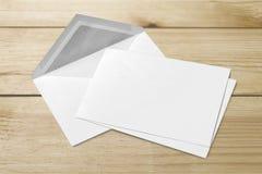 Tomt vitt kuvert och kort på träbakgrund fotografering för bildbyråer