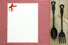 Tomt vitt menytecken på röd rutig bordduk med den gjutjärnskeden och gaffeln Royaltyfri Foto