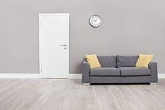 Tomt väntande rum med en modern grå soffa Fotografering för Bildbyråer