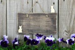 Tomt wood tecken med purpurfärgad flowersm (pansies) Arkivfoto