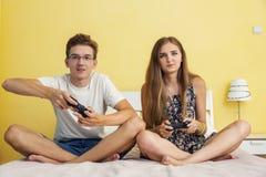 Tonår pojke och flicka som spelar den modiga konsolen arkivbild