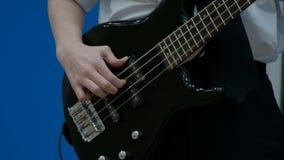 Tonårig bas- gitarrist för grabb som spelar en svart elektrisk gitarr Närbild Fingrarna av en tonåring drar rader på en elbas stock video