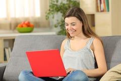 Tonårig bläddra internet i en röd bärbar dator på en soffa fotografering för bildbyråer