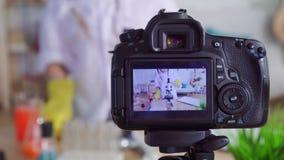 Tonårig bloggeryoutuber för flicka i ett vitt lag och skyddsglasögon i labb, läxa som ser in i ett mikroskop lager videofilmer