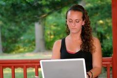 Tonårig flicka bak den horisontalbärbara datorn utomhus Royaltyfria Foton