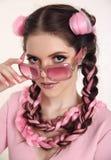 Tonårig flicka för brunett med två franska flätade trådar från rosa kanekalon, f royaltyfri foto