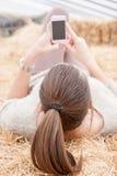 Tonårig flicka för brunett som överför en text som ligger på höstackar Royaltyfri Foto