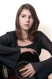 Tonårig flicka för ung brunett som spelar den akustiska gitarren som isoleras på vit Royaltyfria Foton