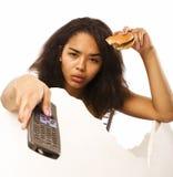 Tonårig flicka för ung fet afrikansk amerikan med fjärrkontrollen Royaltyfria Bilder