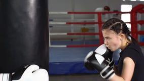 Tonårig flicka i boxninghandskar på boxningutbildning långsam rörelse arkivfilmer