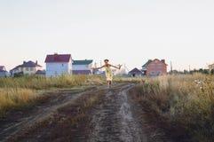 tonårig flicka i en gul klänning som kör på fältet, sommar arkivfoton