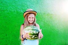 Tonårig flicka i en sugrörhatt som rymmer en stor vattenmelon Flickateenag Arkivfoton