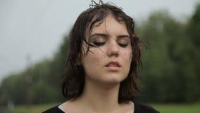 Tonårig flicka i fördjupning i regnet lager videofilmer