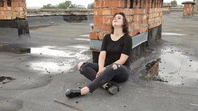 Tonårig flicka i fördjupningen som sitter på taket av en byggnad lager videofilmer