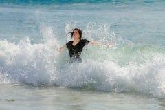 Tonårig flicka i havet som vänder mot kusten med armar utsträckt B royaltyfri bild