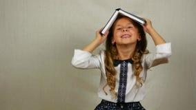 Tonårig flicka i likformign som spelar med boken på huvudet Den lilla studenten täcker huvudet med den öppna boken lager videofilmer