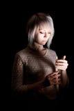 Tonårig flicka i mörkret med en stearinljus, skräck på hennes framsida som ner ser Royaltyfri Foto
