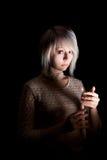 Tonårig flicka i mörkret med en stearinljus, skräck på hennes framsida som ser kameran Arkivbilder