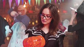 Tonårig flicka i ond häxadräkt med enlykta i hennes händer stock video