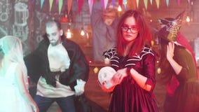 Tonårig flicka i onda danser för en tjuserskadräkt på ett halloween parti arkivfilmer