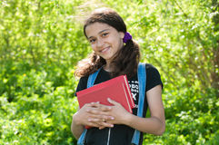 Tonårig flicka med böcker på naturen Fotografering för Bildbyråer