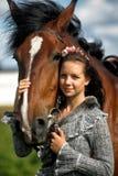 Tonårig flicka med den bruna hästen Fotografering för Bildbyråer