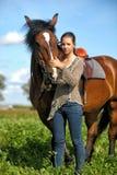 Tonårig flicka med den bruna hästen Royaltyfri Foto