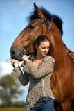 Tonårig flicka med den bruna hästen Arkivfoto