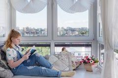 Tonårig flicka med den inomhus boken Fotografering för Bildbyråer