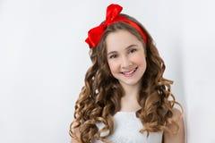 Tonårig flicka med den röda pilbågen på huvudet Royaltyfri Fotografi