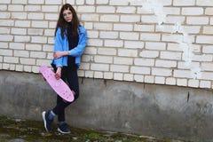 Tonårig flicka med det rosa encentmyntskridskobrädet utomhus arkivbilder