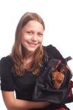 Tonårig flicka med en hund i påse Arkivfoton