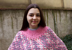 Tonårig flicka med en virkningponcho Royaltyfria Bilder