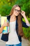 Tonårig flicka med exponeringsglas och böcker Royaltyfria Bilder