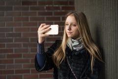 Tonårig flicka med långt hår med en smartphone Arkivfoton