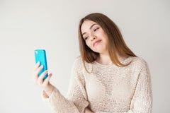 Tonårig flicka med långt hår som talar på Skype på din telefon royaltyfri fotografi