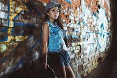 Tonårig flicka med skridskobrädet, stads- livsstil royaltyfri bild