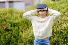 Tonårig flicka med virtuell verklighethörlurar med mikrofon royaltyfri bild