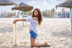 Tonårig flicka på stranden som spelar med sand royaltyfri fotografi