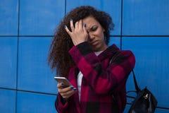 Tonårig flicka som överdrivet hemma sitter på telefonen han är ett offer av sociala nätverk för online-pennalismstalkeren Royaltyfri Fotografi