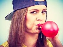 Tonårig flicka som blåser den röda ballongen Royaltyfri Fotografi