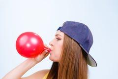 Tonårig flicka som blåser den röda ballongen Royaltyfri Bild