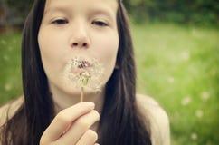 Tonårig flicka som blåser på en maskrostoning Arkivbilder