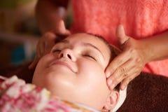 Tonårig flicka som får en massage under hennes ansiktsbehandling på brunnsorten royaltyfri foto