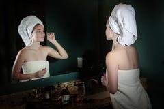 Tonårig flicka som gör makeup i badrum Royaltyfria Bilder