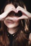 Tonårig flicka som gör symbol för hjärtaformförälskelse med händer Arkivbilder