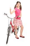 Tonårig flicka som ger upp tummen och står vid en cykel Arkivfoton